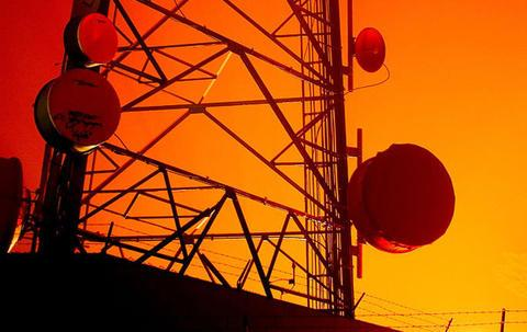 silhouette of a communications tower in front of an orange sky