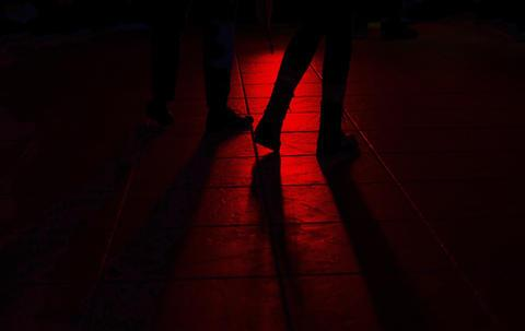 black legs silhouetted in red and black street