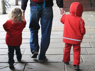 a man holding the hands of two small children in red coats