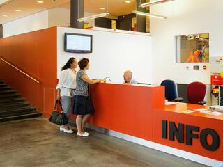 people standing at an organge information counter