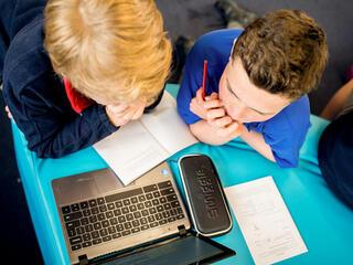 two boys working at a laptop on a blue desk