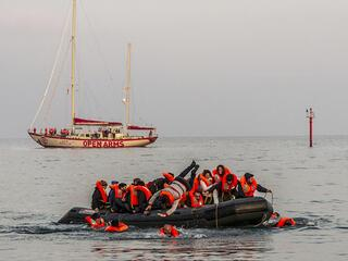 asylum seekers wearing life vests in an inflatable boat