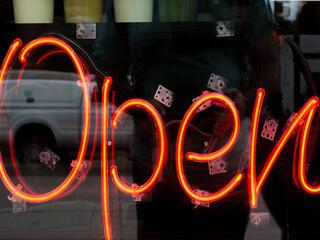 """open"" neon sign in orange on black"