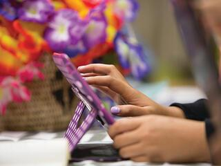 hand near purple tablet with flowers in background