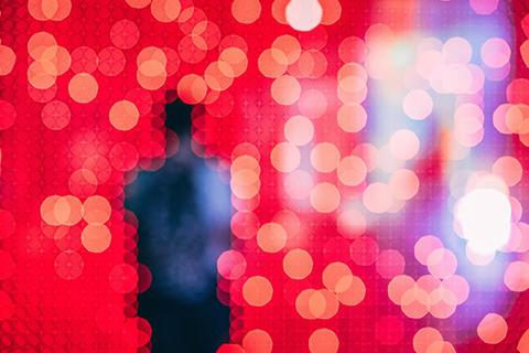 figure in front of a red pixelated background